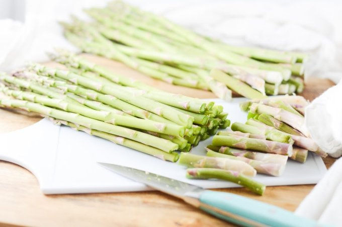 uncooked asparagus spears lying flat on a bench with the woody ends being trimmed