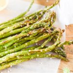 air fryer asparagus lying on parchment paper with sprinkles of sea salt on top
