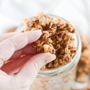 Banana bread granola being lifted in clusters from a glass mason jar