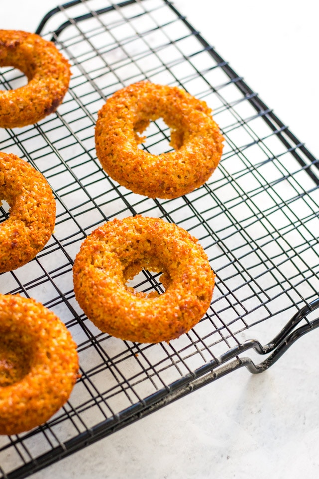 baked banana donuts on a black cooling rack against a white background