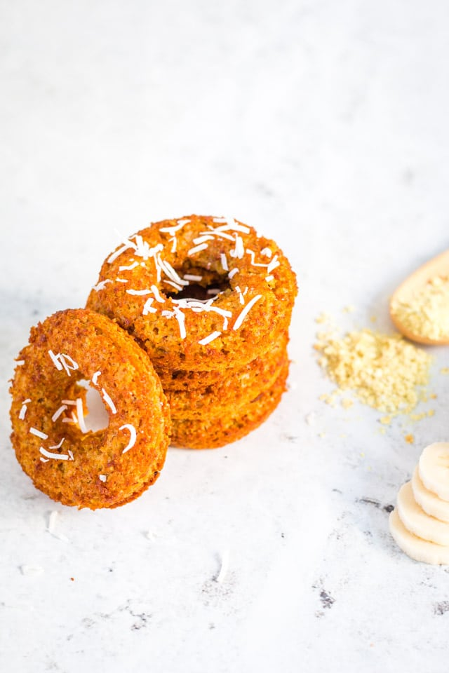 stack of banana donuts topped with coconut flakes on a white background