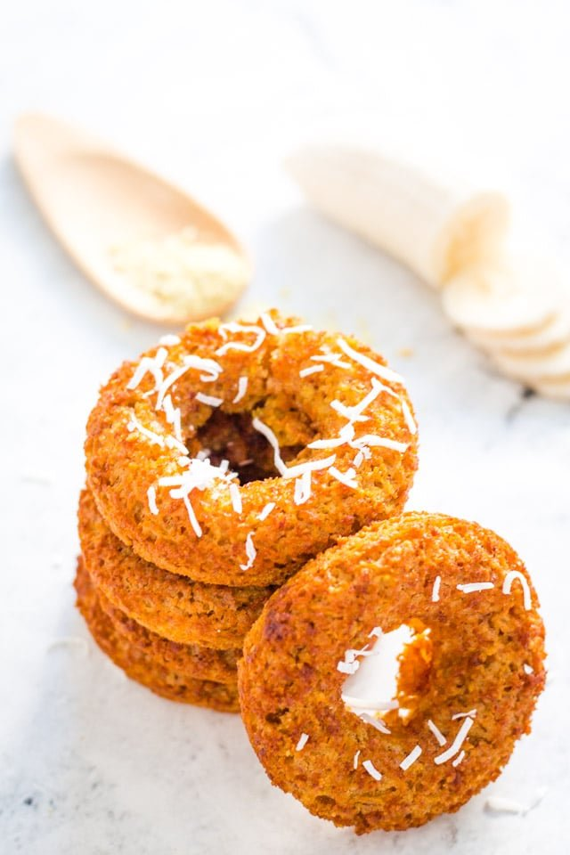 stack of banana donuts with a sprinkle of coconut on top and a spoonful of raw oats in the background
