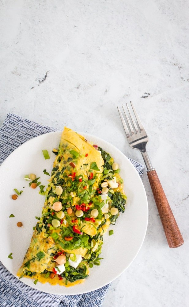 spinach and veggie omelette on a white plate