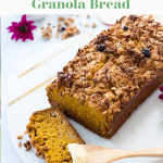 pumpkin bread topped with granola and placed on a platter plate on a white background