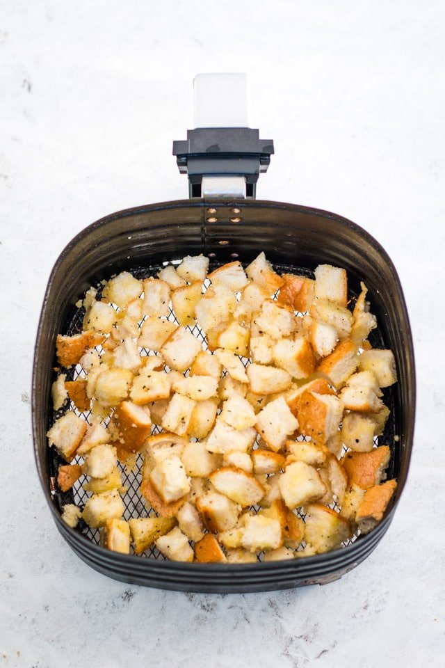 air fryer basket filled with an even layer of bread chunks soaked in olive oil, salt, pepper, garlic and parsley powder