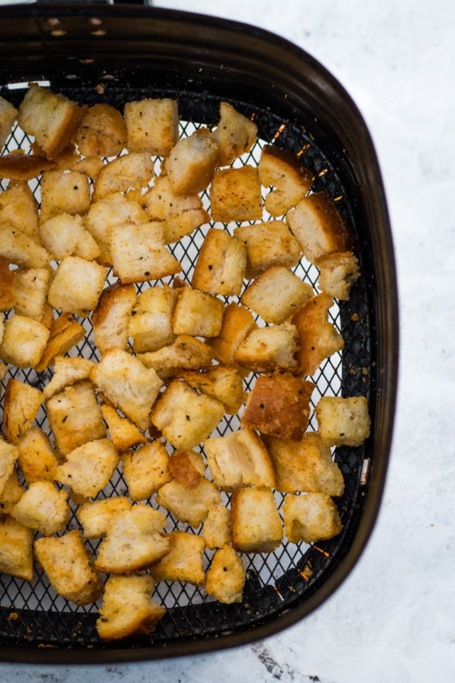 Up close shot of the basket of an air fryer with perfectly golden air fryer croutons