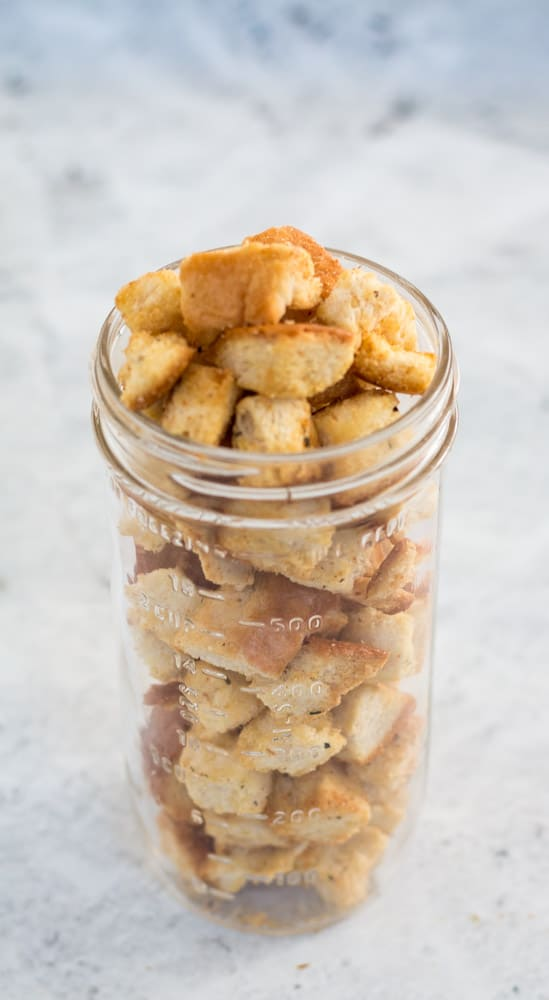 tall glass mason jar filled to overflowing with croutons against a grey background