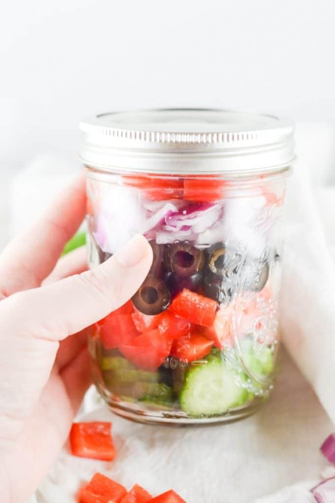 hand holding a glass mason jar with Greek salad ingredients inside