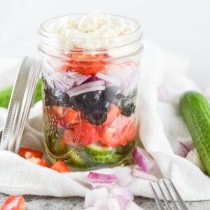 glass mason jars with greek salad ingredients layered inside
