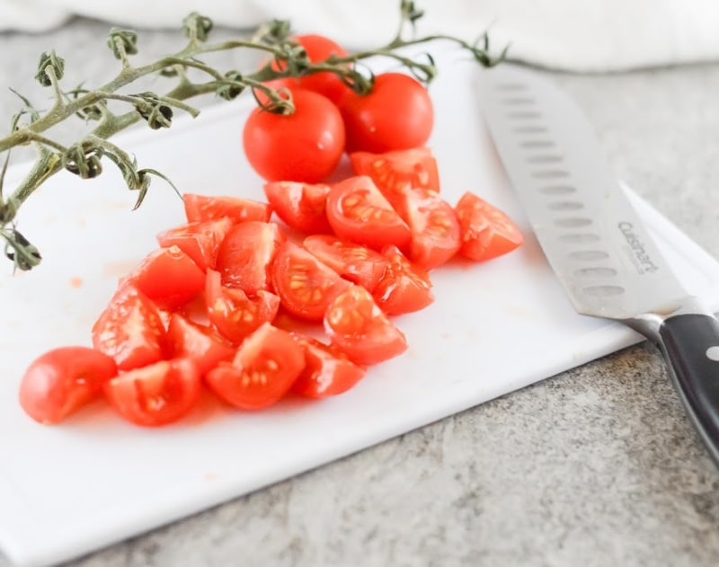 cherry tomatoes on a white chopping board cut into quarters