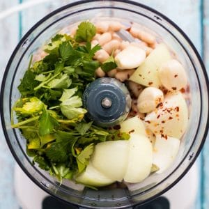 food processor with onion, garlic, beans, parsley and chili flakes