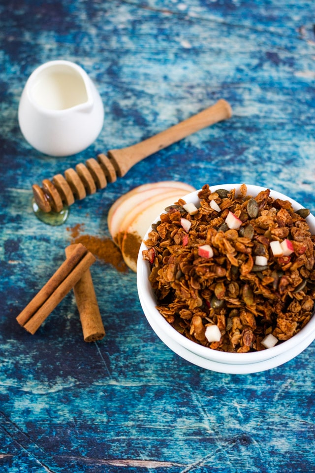 Apple Cinnamon Granola in a white bowl against a dark blue background with a little pot of milk, honey stick and cinnamon sticks