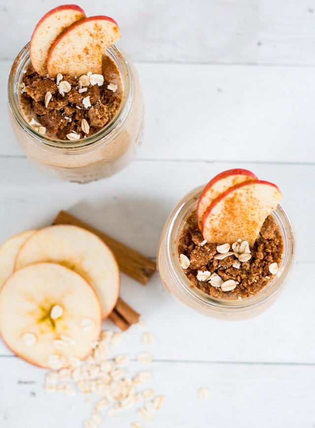 2 fall smoothies in glass mason jars, topped with apple slices and ground cinnamon and surrounded by apple discs and cinnamon sticks against a white background