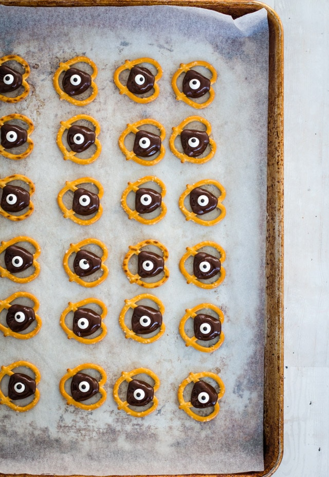 baking tray loaded with pretzels topped with chocolate and a google eye