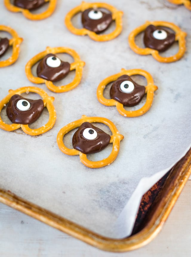 a baking tray with baking paper and cooling halloween pretzel bites