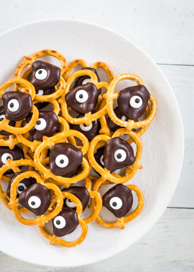 A white plate topped with a stack of halloween pretzels with google eyes and a chocolate topper