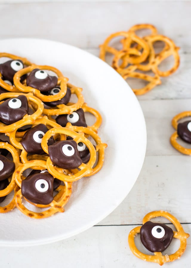 pretzels topped with chocolate and a googly eye on top of a white plate