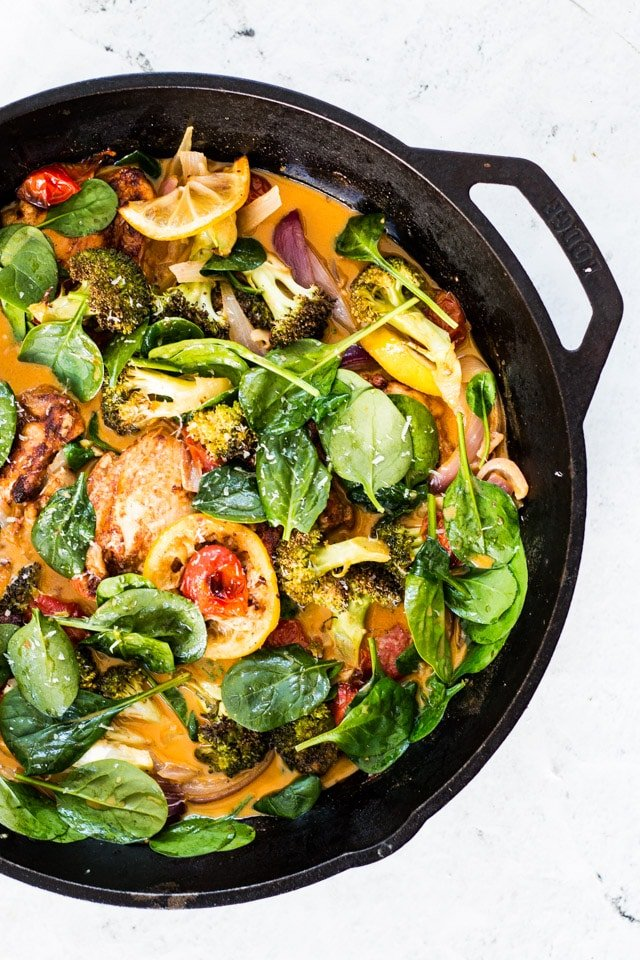 Baby spinach being added to a skillet with chicken and vegetables in a cream sauce