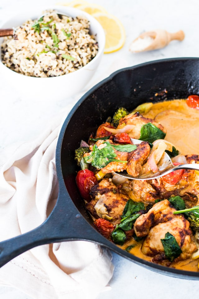 A silver spoon taking a big spoonful of lemon garlic butter chicken from a large black cast iron skillet