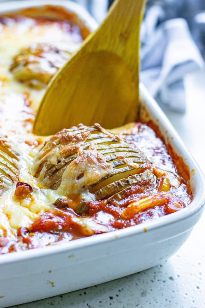 Hasselback potatoes being scooped out of a casserole dish with a wooden spoon