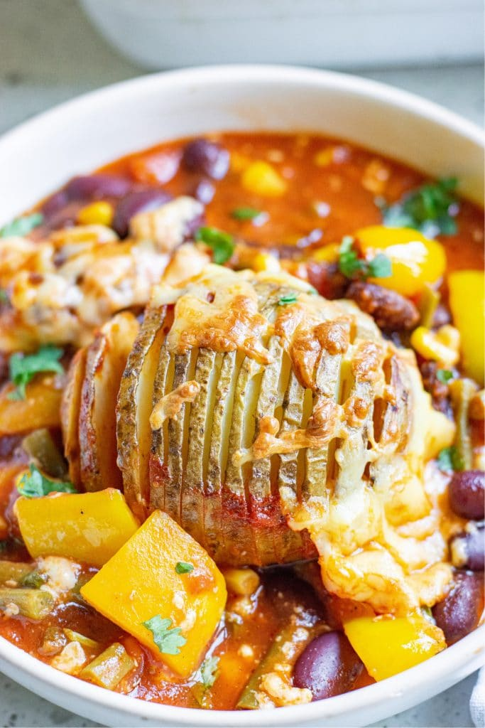 Up close shot of a hasselback potato in a bowl of chili