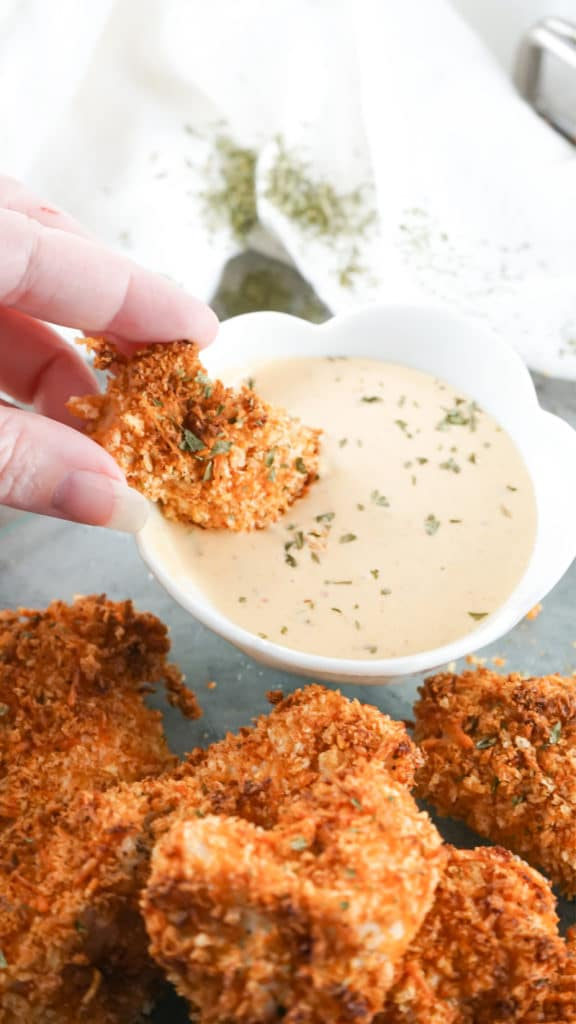 Air Fryer Chicken Nuggets being dipped into a pinkish sauce in a white bowl