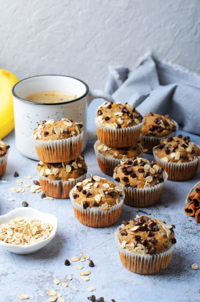 Stacks of chocolate chip muffins with a cup of coffee and some bananas in the background
