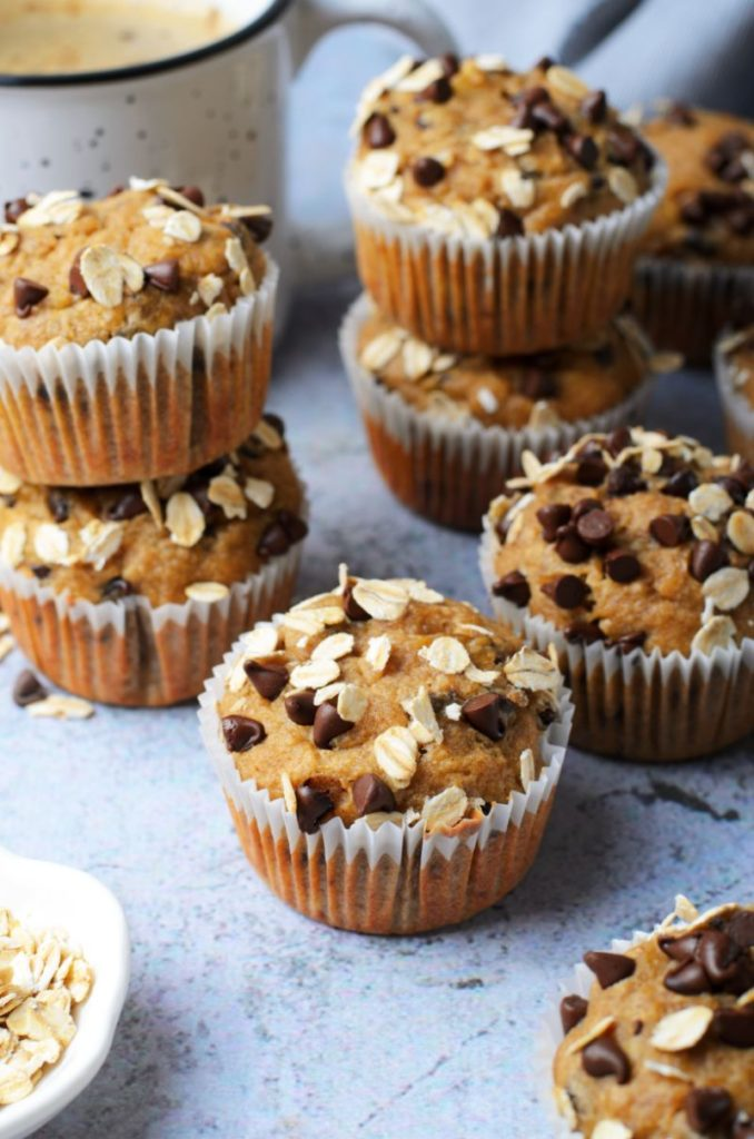 Peanut butter chocolate chip banana oatmeal muffins against a light blue background with a coffee and loose oats scattered around