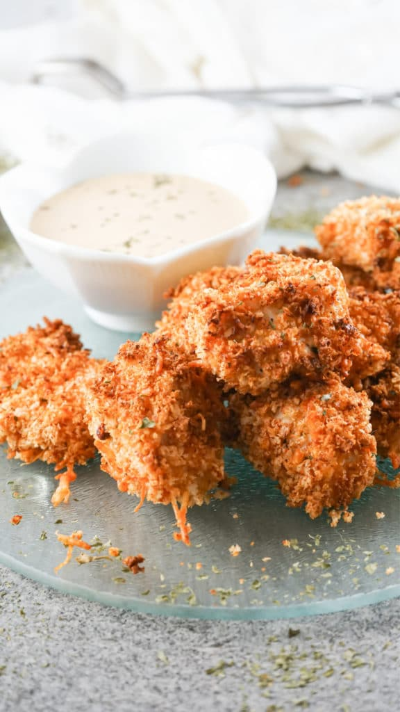 Air Fryer Chicken Nuggets piled onto a glass serving dish with a white bowl in the background containing a dipping sauce