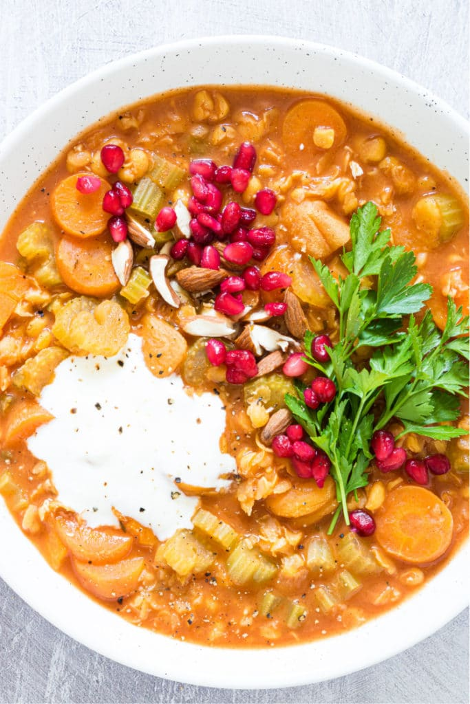 up close overhead shot of a white bowl containing a split pea soup topped with pomegranate arils and yogurt