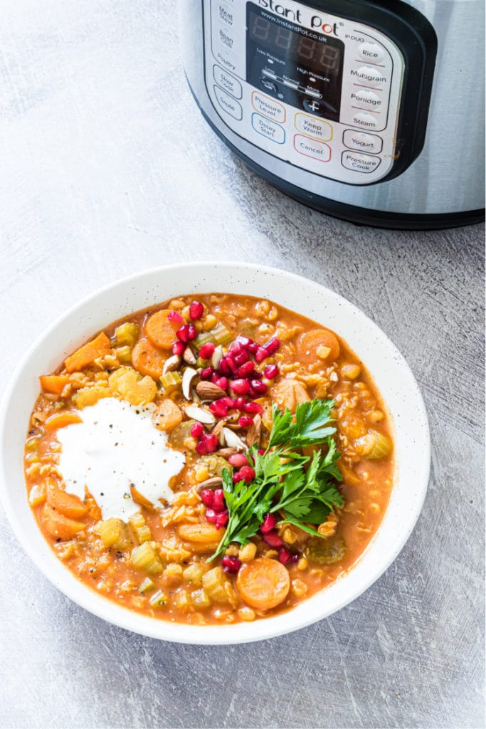 Vegan split pea soup served in a white bowl beside an  instant pot