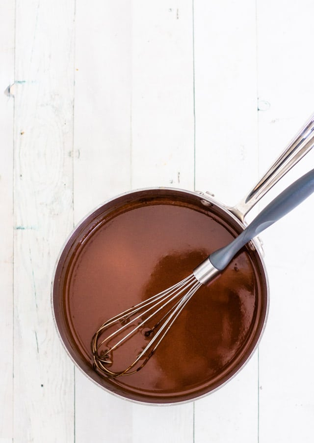 A small saucepan with a whisk whisking together the ingredients for peppermint creamer