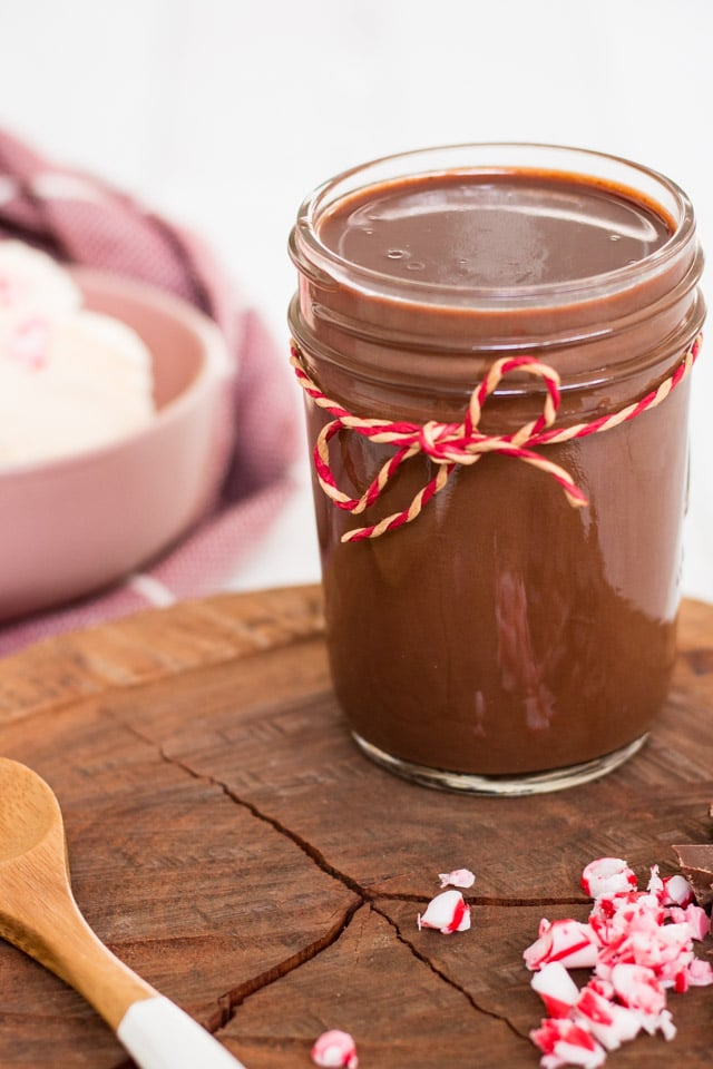Up close shot of chocolate sauce on a wooden board with chopped up peppermint candy canes and a pink bowl of ice cream in the background