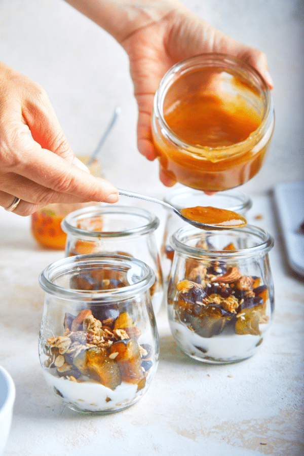Fruit yogurt parfait being constructed: ingredients have been layered in two small glass jars and some honey is being drizzled on top