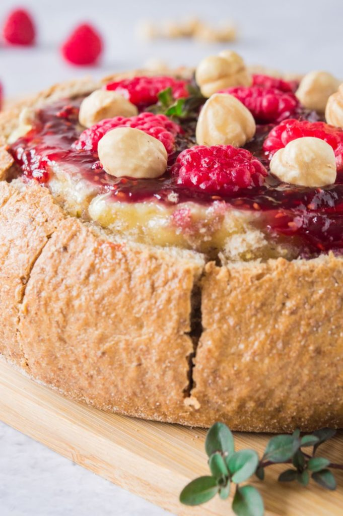 Baked brie in a whole meal cob loaf topped with raspberries and hazelnuts on a wooden board