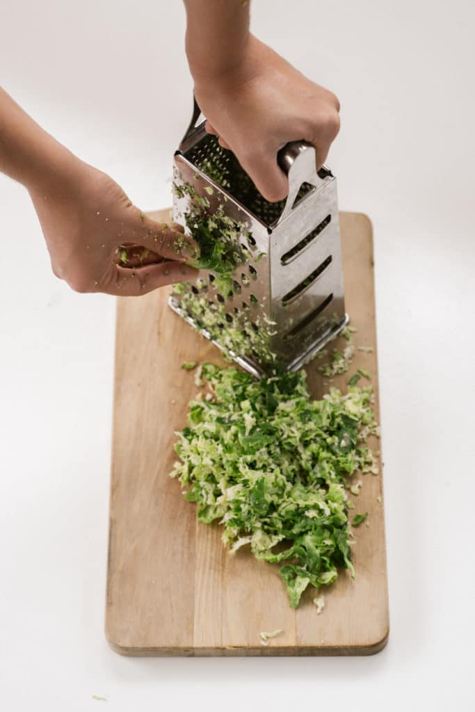Side view of a box grater being used to grate brussels sprouts