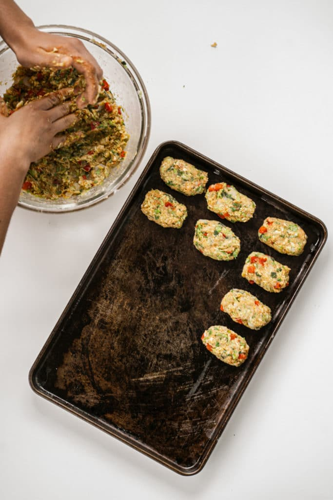 uncooked vegetable tots being line on an oiled baking tray with a hand getting more mixture from a glass bowl on the side