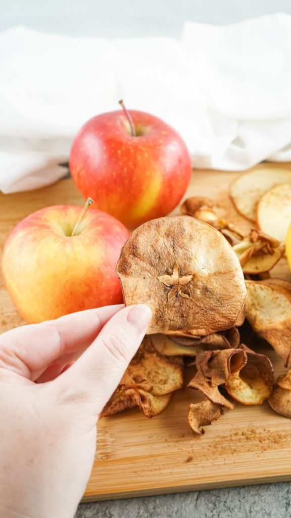 air fryer apple chips being picked up from a wooden board with fresh apples in the background