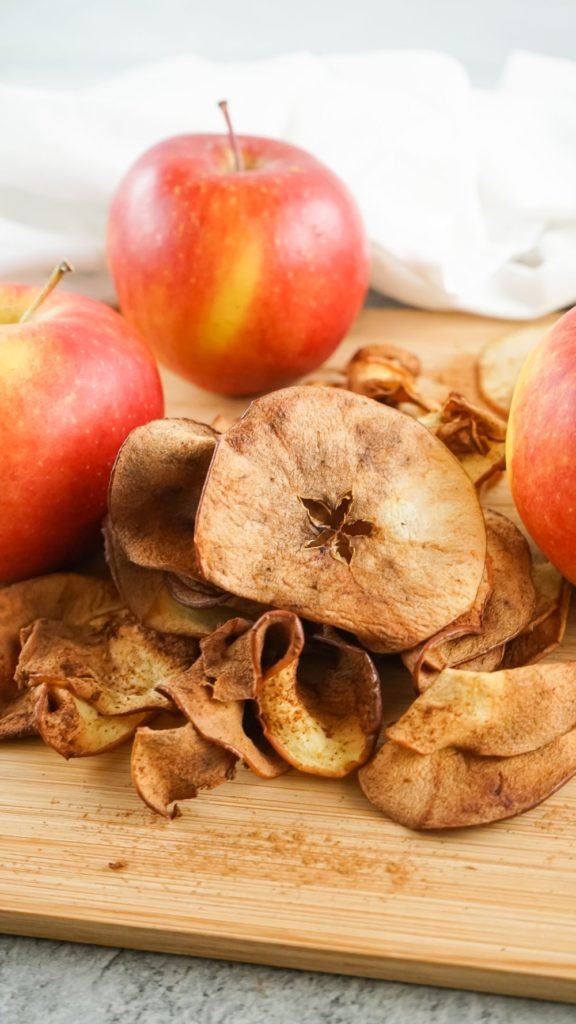A stack of browned apple crisps on a wooden board with fresh apples in the background
