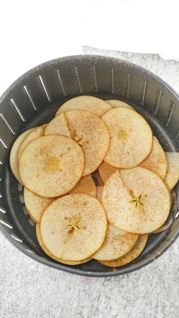 apple slices arranged in the basket of an air fryer