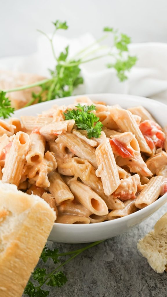 front angle shot of a bowl of creamy pasta with torn baguette on the side