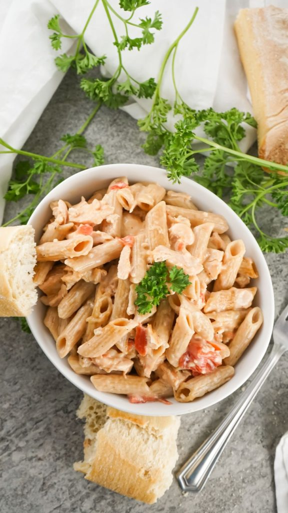 overhead shot of a bowl of creamy pasta served in a white bowl with some crunchy bread and parsley on the side