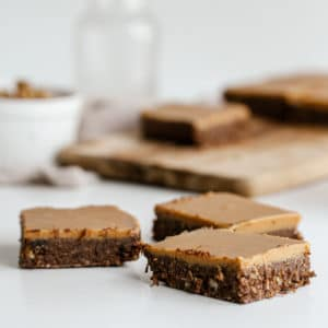 up close shot of vegan brownies on a white background with a chopping board in the background