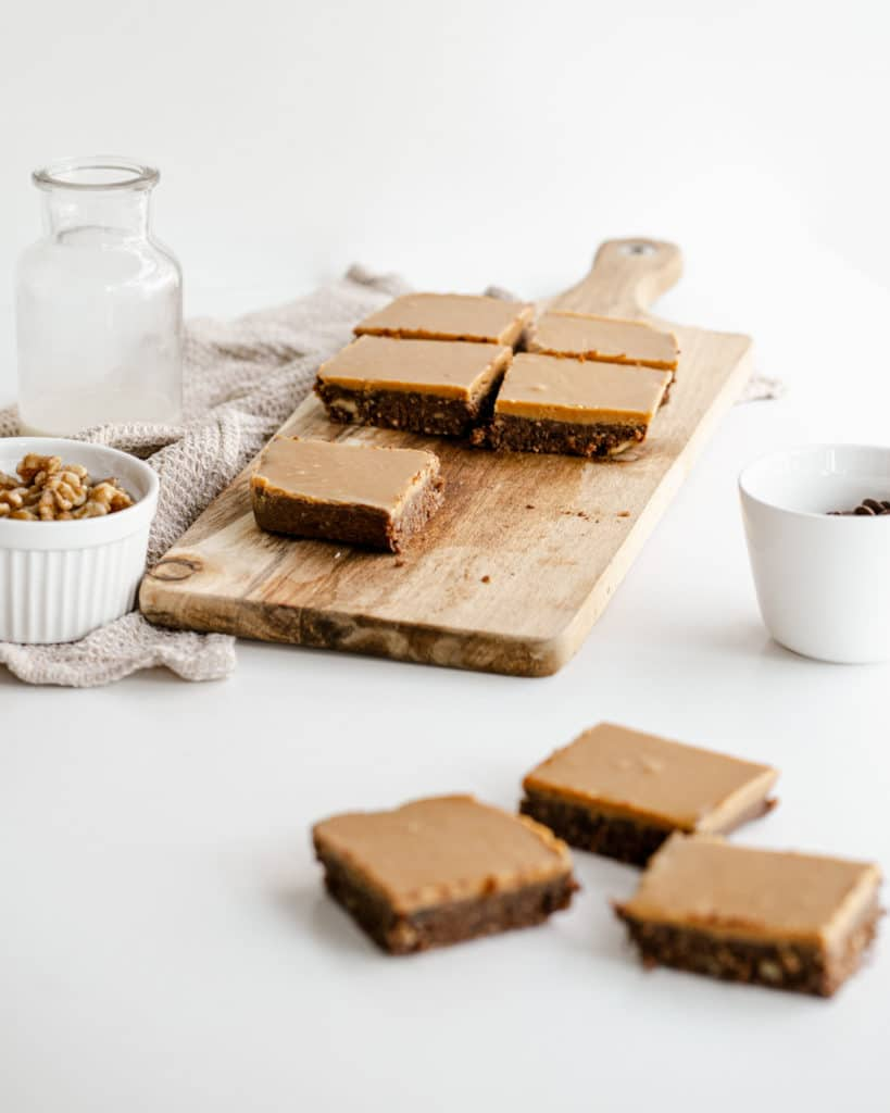 brownie slices on a wooden chopping board with bowls of nuts on the side against a white background.