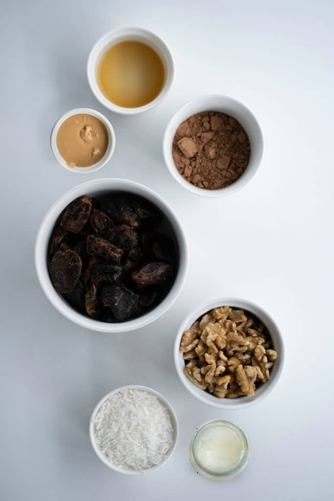 Overhead shot of ingredients for vegan no-bake brownies in white bowls against a white background