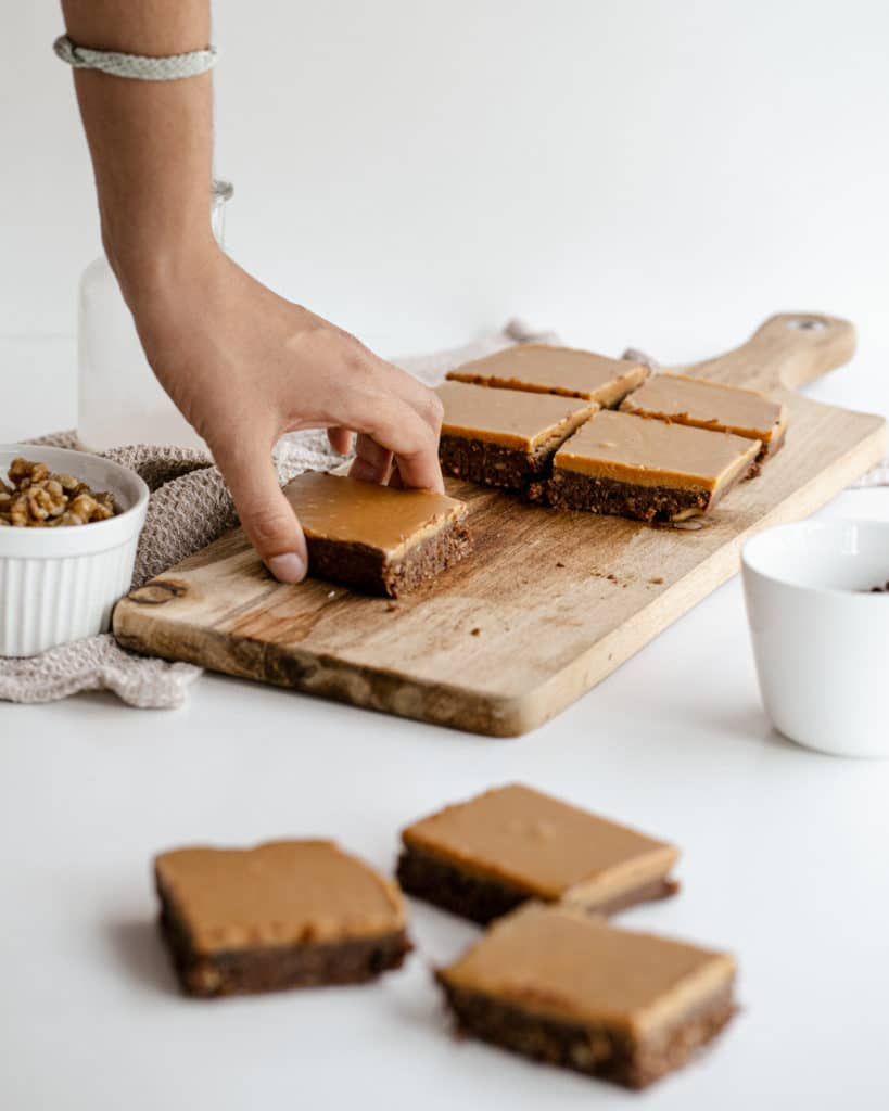 A hand lifting a slice of a vegan brownie from a wooden chopping board