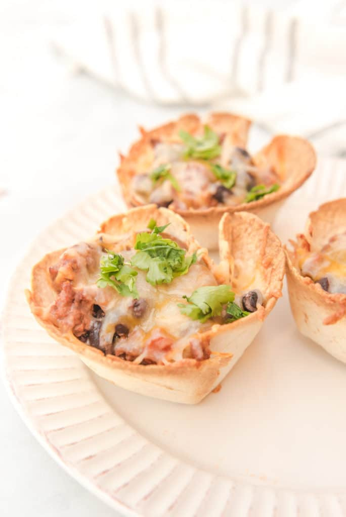 beef enchiladas baked in muffin tin tortillas and topped with cilantro served on a white plate