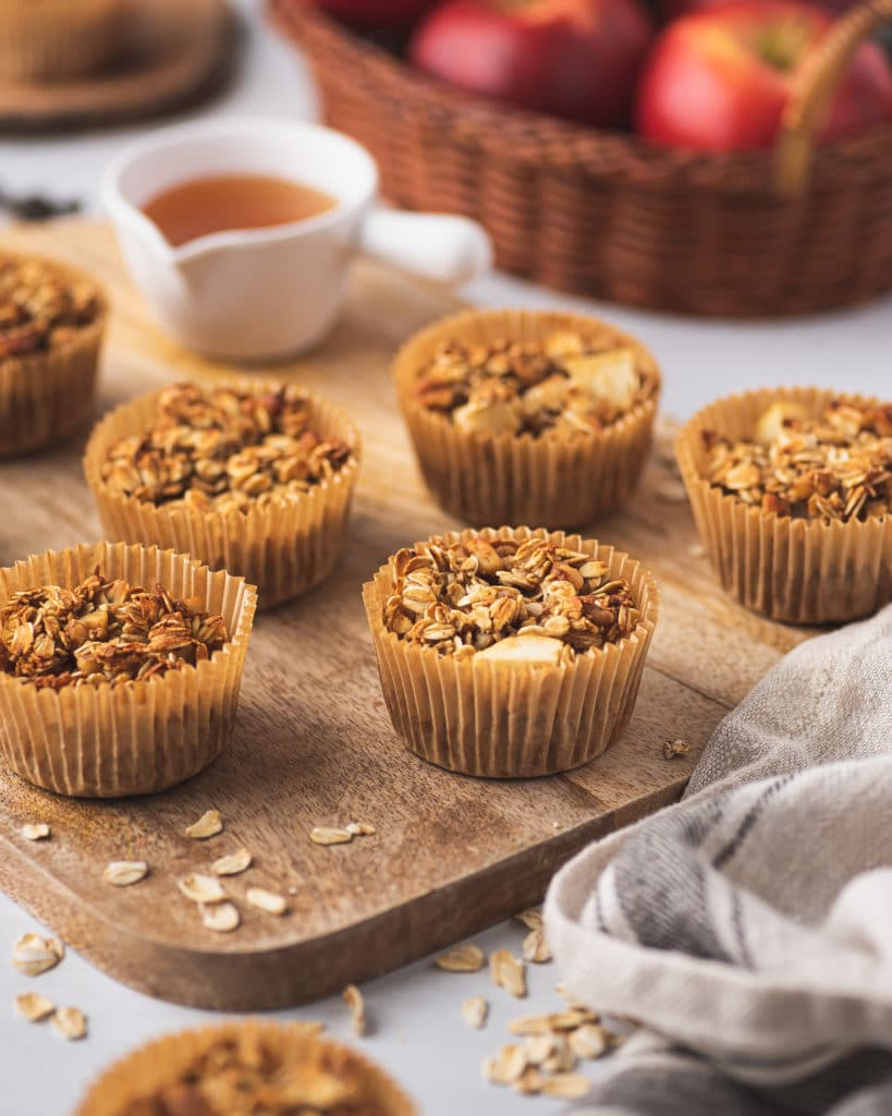 wooden board containing apple cinnamon oatmeal cups with fresh apples and honey in the background