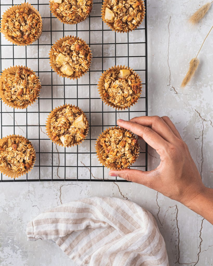 overhead shot of a hand reaching for a baked apple cinnamon oatmeal muffin on a cooling rack