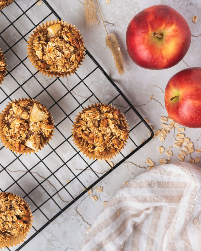 Apple cinnamon muffins on a cooling tray with fresh apples, cinnamon and oats on the side